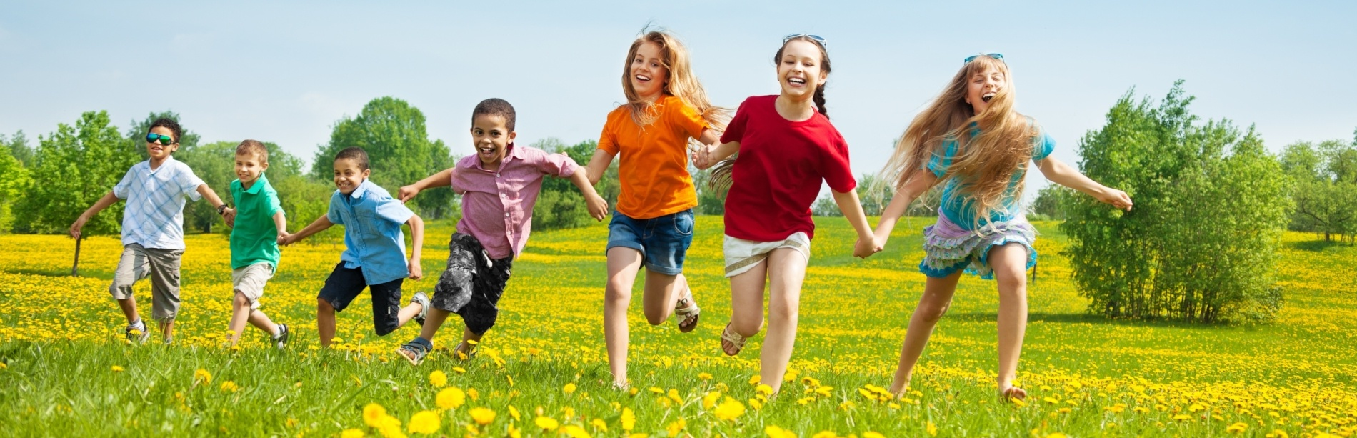 Children playfully running through a field of dandelions