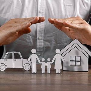 Hands covering a family, their car, and their home
